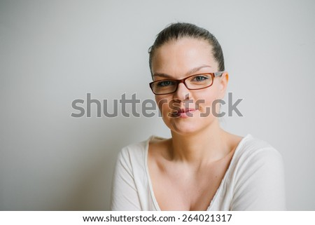 Portrait of a beautiful brunette young woman with clear skin and reading glasses, smiling, white background - stock photo
