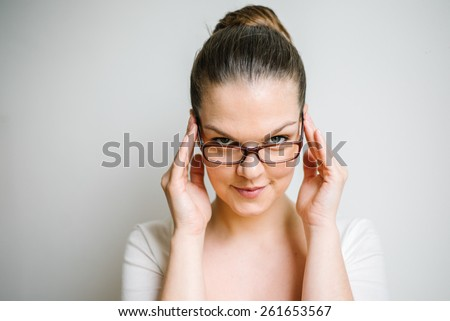 Portrait of a beautiful brunette young woman with clear skin reading glasses, white background - stock photo