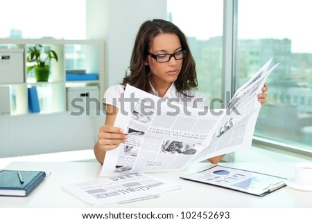 Portrait of a beautiful business lady reading newspaper - stock photo