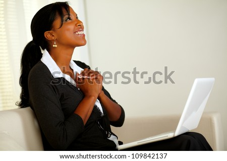 Portrait of a beautiful business woman on black suit smiling and looking up and thanking while sitting on sofa at home indoor - stock photo