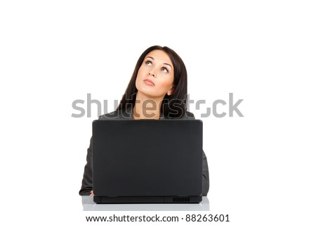 Portrait of a beautiful business woman sitting at the desk with laptop think looking up to empty copy space, isolated over white background - stock photo