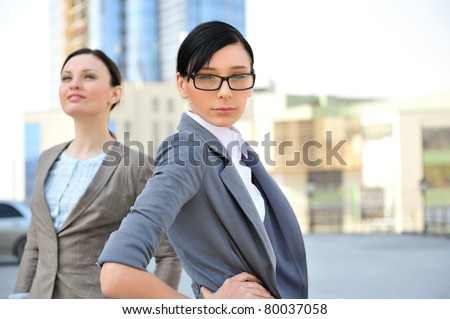 Portrait of a beautiful business woman with a female colleague in the background against constructing office building. - stock photo