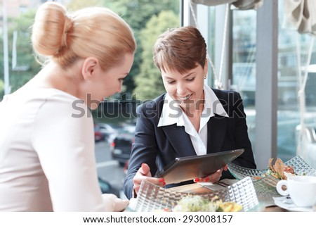 Portrait of a beautiful businesswoman wearing a formal suit sitting at the table showing something on her tablet to colleague sitting back to us, in a restaurant during business lunch, selective focus - stock photo