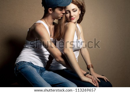 portrait of a beautiful casual couple in jeans sitting together over wooden background. boy hugging girl. studio shot - stock photo