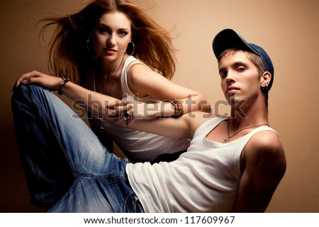 portrait of a beautiful casual couple in jeans sitting together over wooden background. studio shot - stock photo