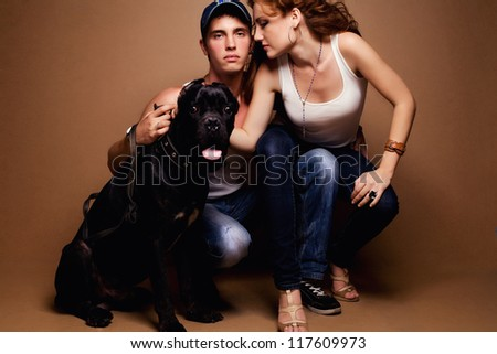 portrait of a beautiful casual couple in jeans sitting together with big black dog over wooden background. studio shot - stock photo