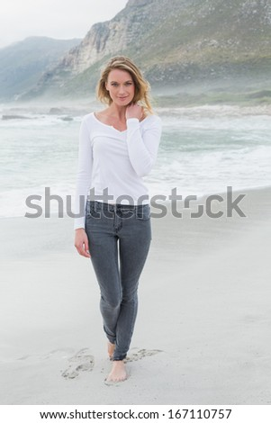 Portrait of a beautiful casual young woman standing at the beach - stock photo