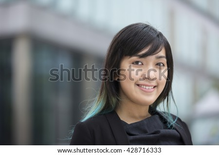 Portrait of a beautiful Chinese businesswoman in smart business suit standing outside in modern city. - stock photo