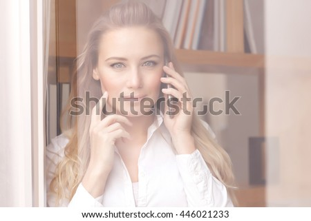 Portrait of a beautiful confident business woman on the phone, standing near windows at the office, young female at work - stock photo