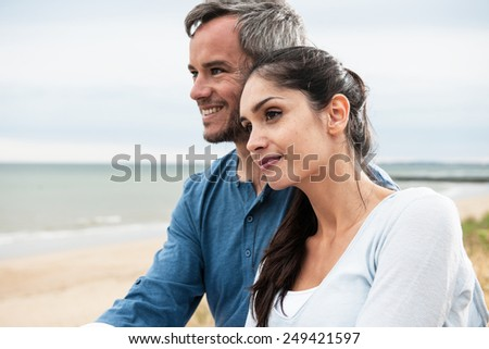 Portrait of a beautiful couple at the beach wearing casual clothes and looking at the ocean - stock photo