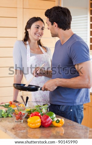 Portrait of a beautiful couple cooking with a pan in their kitchen - stock photo