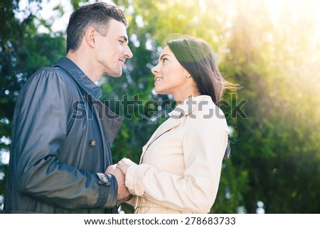 Portrait of a beautiful couple flirting in park and looking at each other - stock photo