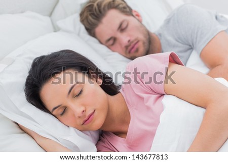 Portrait of a beautiful couple sleeping in bed - stock photo