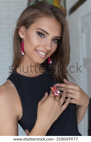 portrait of a beautiful cute gentle beautiful young girl with snow-white smile with bright makeup in black evening gown with jewelry design - stock photo