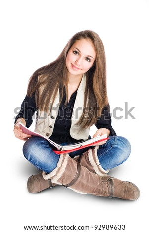 Portrait of a beautiful cute young student girl sitting and reading. - stock photo