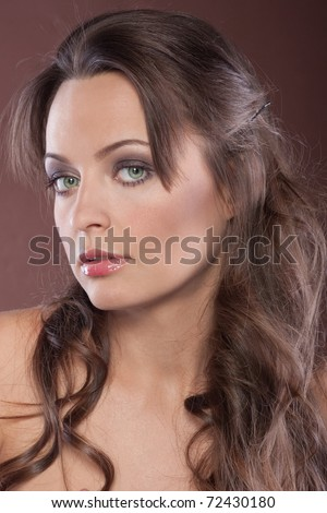 Portrait of a beautiful dark-haired girl on a chocolate background. - stock photo
