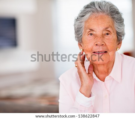 Portrait of a beautiful elder woman smiling at home - stock photo