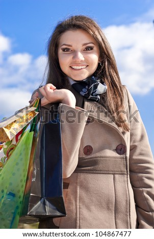 Portrait of a beautiful Elegant Happy smiling young woman carrying some shopping bags on a bright sunny day of spring, autumn or winter with blue sky on the background - stock photo