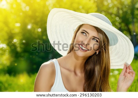 Portrait of a beautiful elegant young woman in light white dress and hat in the summer park. Beauty, fashion. Holidays.  - stock photo