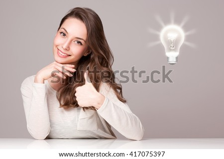 Portrait of a beautiful expressive young brunette with light bulb idea sign. - stock photo