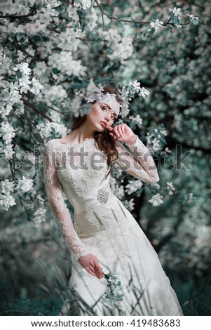 Portrait of a beautiful fashion bride wedding dress , sweet and sensual . Wedding makeup and hair . Flowers background. Art in a contemporary style. Against the background of blooming apple orchards . - stock photo