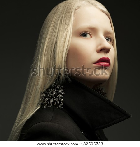 Portrait of a beautiful fashionable model with natural blond hair and great make-up posing over dark gray background. Close up. Studio shot - stock photo