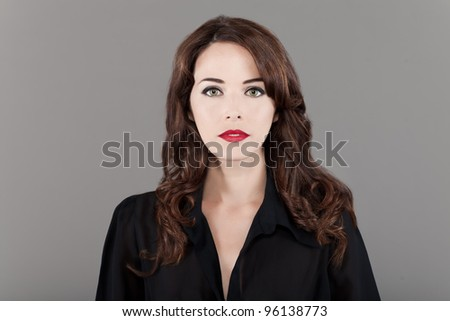 Portrait of a beautiful fashionable woman in studio on gray background - stock photo