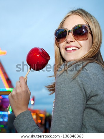 Portrait of a beautiful fashionable young woman in an amusement park arcade ground wearing sunglasses with reflections of rides and lights, holding a red caramel apple during evening night time. - stock photo