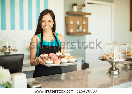 Portrait of a beautiful female business owner showing some of her freshly baked cupcakes and smiling - stock photo