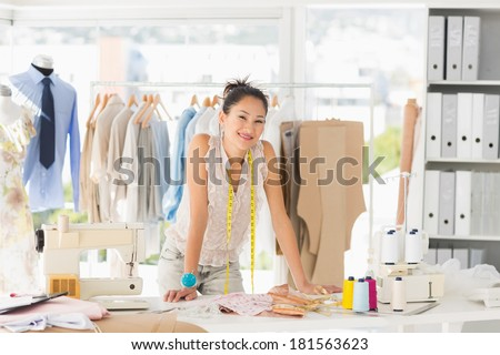 Portrait of a beautiful female fashion designer with rack of clothes in the store - stock photo