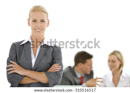 Portrait of a beautiful female manager with business team working together in the background. - stock photo