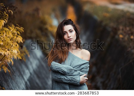 Portrait of a beautiful female model in sweater at autumn park outdoor. sensitive look. close up - stock photo