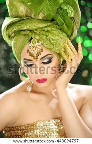 Portrait of a beautiful female model in traditional ethnic costume with heavy jewellery and makeup - stock photo