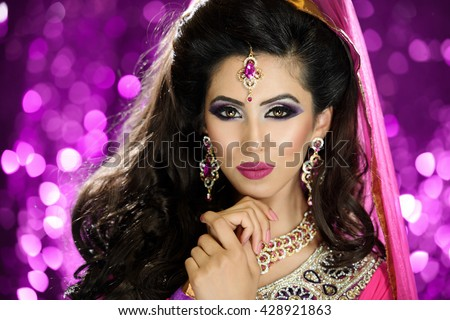 Portrait of a beautiful female model in traditional ethnic indian asian bridal outfit with heavy makeup and jewellery - stock photo
