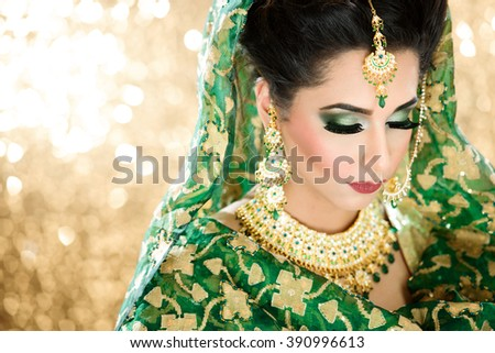 Portrait of a Beautiful Female Model in Traditional Indian Asian Bridal Wedding costume with makeup and jewellery - stock photo