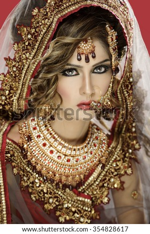 Portrait of a beautiful female model in traditional indian bridal costume with jewellery and makeup - stock photo