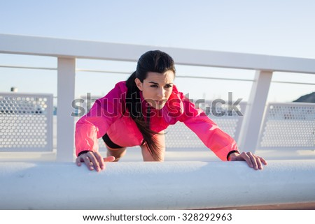 Portrait of a beautiful female runner warming up before began her fitness training outdoors in summer day, charming sportive woman in tracksuit doing stretching exercise before her active jog outside - stock photo