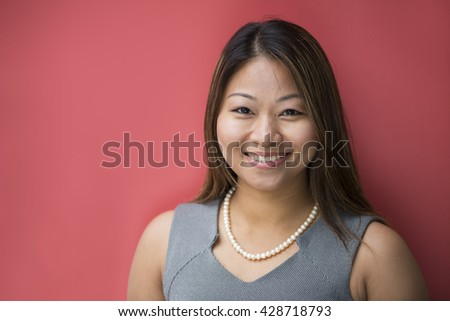Portrait of a beautiful Filipino businesswoman in smart business suit leaning against a red wall.  - stock photo