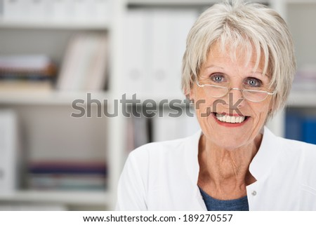 Portrait of a beautiful friendly senior grey-haired lady wearing glasses posing in an office looking at the camera with a lovely smile - stock photo