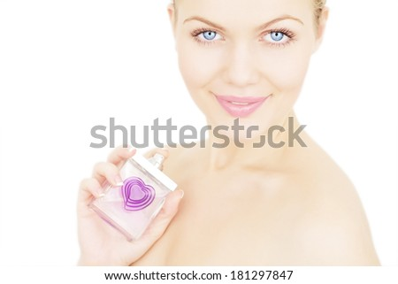 Portrait of a beautiful girl holding a bottle of perfume - stock photo
