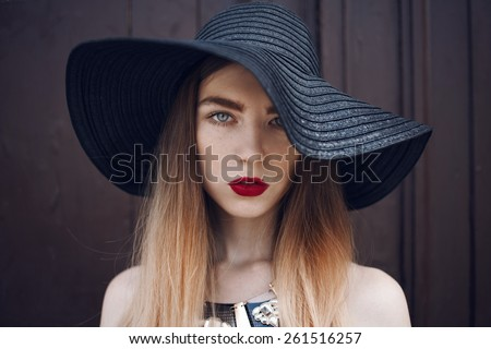 Portrait of a beautiful girl in a black hat with a wide brim and long ombre hairs - stock photo
