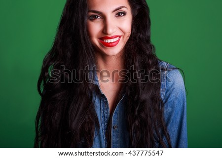 Portrait of a beautiful girl in a blue denim jacket on a green background - stock photo