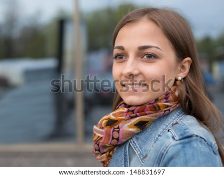 portrait of a beautiful girl in a denim jacket with a scarf on the street - stock photo