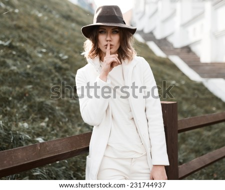 Portrait of a beautiful girl in a fashionable hat and coat in - stock photo