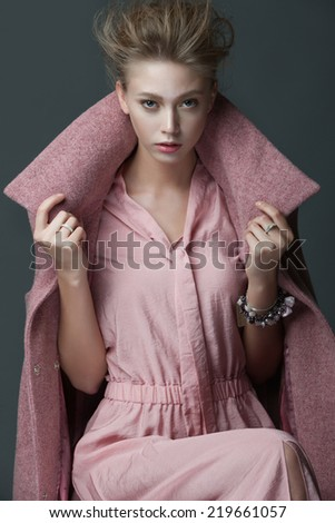 Portrait of a beautiful girl in a pink coat, posing in studio on a gray background - stock photo