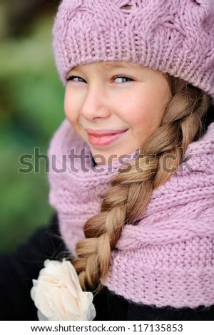Portrait of a beautiful girl in a pink hat and scarf. Long hair. - stock photo