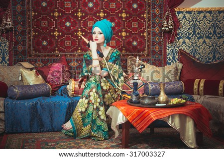 Portrait of a beautiful girl in eastern dress and jewelry. The girl gracefully sitting on cushions among the carpet with a hookah in the hands of - stock photo
