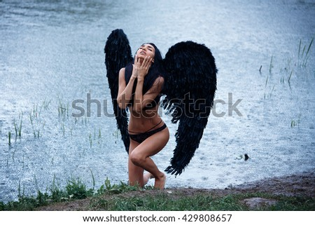 Portrait of a beautiful girl in lingerie bodysuit black wings demon angel nature - stock photo