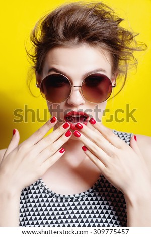 Portrait of a beautiful girl in round glasses on a yellow background in the studio posing surprise - stock photo
