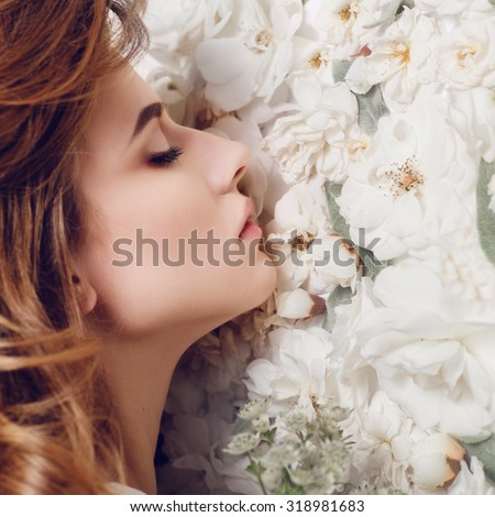 Portrait of a beautiful girl on a background of white flowers - stock photo